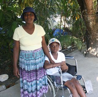 Haitian woman and child wearing hats donated by Maine business, The Little Hat Company.